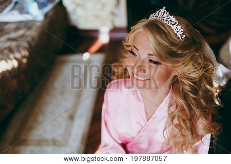 Beautiful Blonde Bride In A Tiara Sits On A Chair