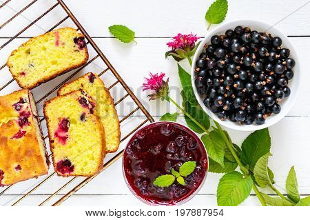 Delicate tasty curd cake with black currant ripe berries and jam on a white wooden background. Top view.