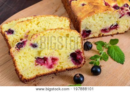 Delicate tasty curd cake with black currant and jam on a dark wooden background.