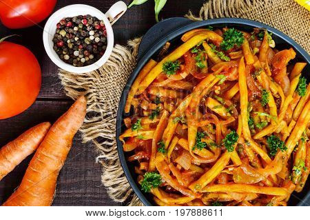 Spicy green beans stewed with onions carrots in tomato sauce. Serve on a cast-iron frying pan on a dark wooden background. Top view.