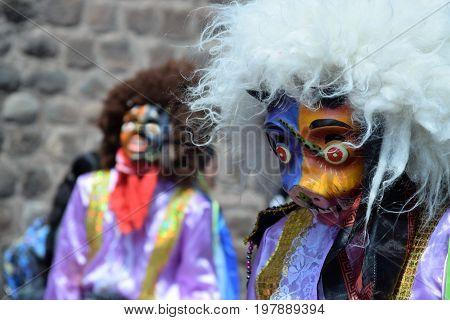 Masked reveler in street festival in Cuzco, Peru
