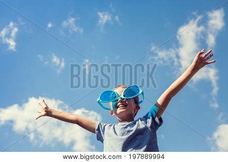 Boy on beach with big sunglasses enjoying the sun on summer vacation
