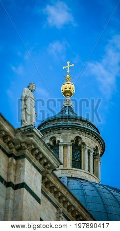 The golden dome and cross on a cathedral in Italy