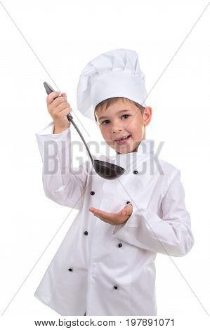 Beautiful smiling little boy in chef's hat with ladle tastes the cooked broth