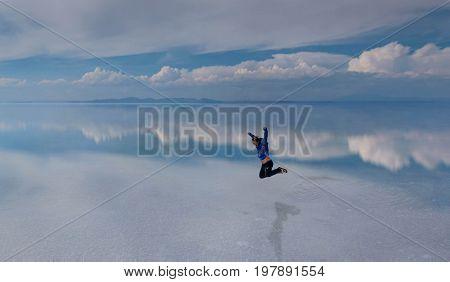 Uyuni, Bolivia- March 25, 2017:Man jumping on the lake Salar de Uyuni Bolivia