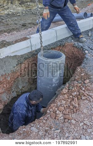 Road Worker In Trench Installing Storm Drain System