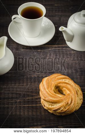 sweets cup of coffee and creamer and teapot on a wooden table