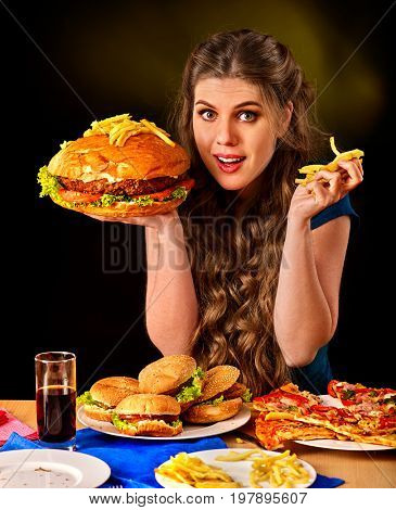Woman eating french fries and hamburger with pizza. Portrait of student consume fast food on table. Girl trying to eat junk on dark background. Table with sandwiches and fried potatoes.
