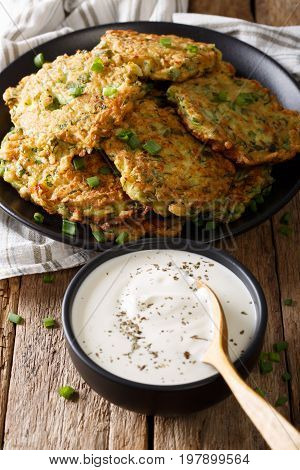Homemade Zucchini Fritters With Greens And Sour Cream Close-up. Vertical