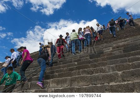 Teotihuacan State of Mexico Mexico - June 1 2014: Visitors in the Temple of the Sun staircase at the Teotihuacan archaeological site in Mexico. Teotihuacan was one of the largest cities in the pre-Columbian Americas.