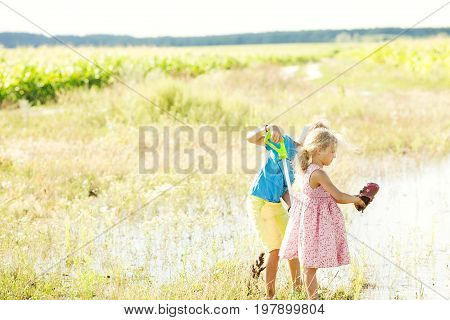 A boy and a girl are showered with water from water pistols. The girl smudged her shoes. Children play water pistols. Brother and sister