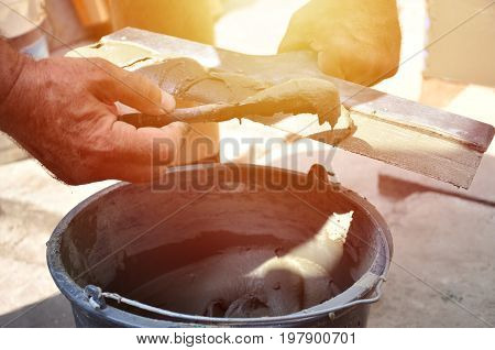 Hands of an old manual worker with wall plastering tools near the bucket with reinforcing mixture. Plastering repair of external walls and corners with a spatula and plaster. Wall insulation poster