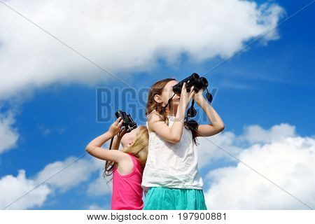 Two Cute Little Girls Looking Through Binoculars On Sunny Summer Day