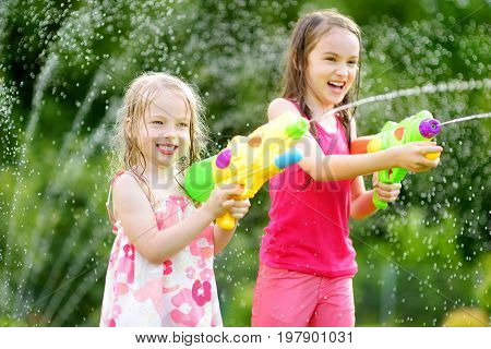 Adorable Little Girls Playing With Water Guns On Hot Summer Day. Cute Children Having Fun With Water