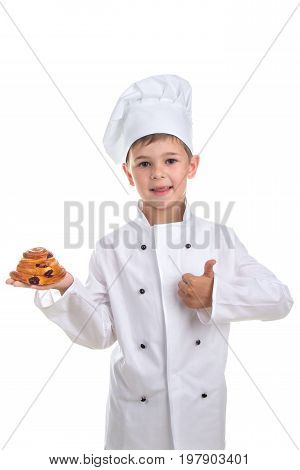 Emotional pretty kid in chef uniform with tasty raisin bun gesturing okay, isolated on white background.