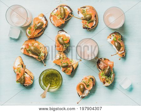 Crostini with smoked salmon, pesto sauce, watercress and capers and pink grapefruit cocktails in glasses over light blue background, flat-lay, top view. Party, catering or fingerfood concept