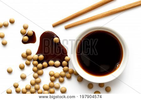 Soya Sauce In White Ceramic Bowl On White From Above With Wooden Chopsticks. Spilled Soya Sauce And