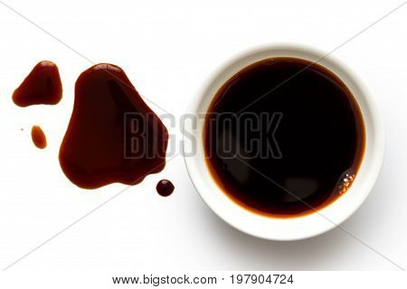Soya Sauce In White Ceramic Bowl Isolated On White From Above. Spilled Soya Sauce.