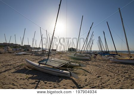 group of catamaran boats in the sun on the beach Els Terrers in Benicassim Castellon Valencia Spain Europe. Blue clear sky and Mediterranean Sea