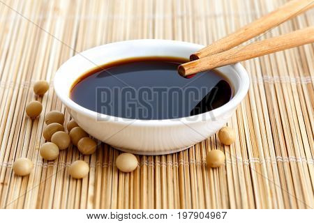 Soya Sauce In White Bowl On Bamboo Mat With Chopsticks Resting On The Bowl And Spilled Soya Beans.