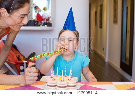 Child Blowing Party Blower Next To Mother And Cake
