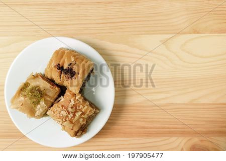 Top View of Baklava pastries on white plate served on wooden table, with free space for design and text