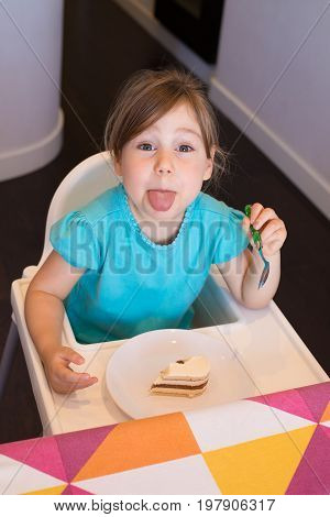 Little Child Eating Cake Sticking Out Tongue