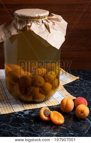 Juicy Harvested Apricots And Big Glass Jar With Canned Apricot Compote On Dark Marble..