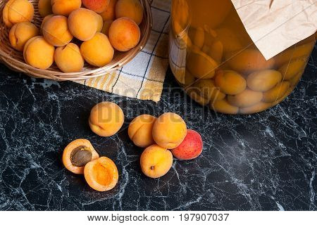 Fresh Organic Harvested Apricots In Basket And Big Glass Jar With Canned Apricot Compote On Dark Mar