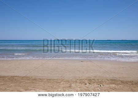 landscape of Mediterranean Sea from sand shore beach of Grao of Castellon in Valencia Spain Europe. Blue clear sky and great cargo boats sailing in the horizon