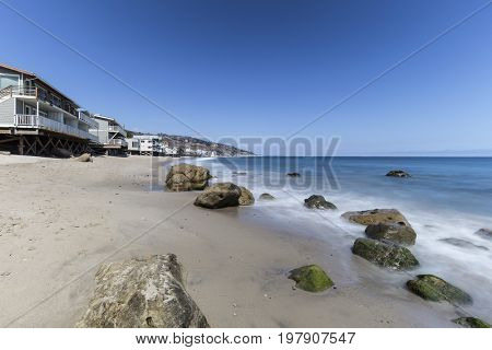 Oceanfront homes with motion blur water movement at Carbon Beach in Malibu, California.
