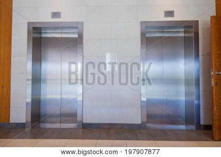 front view of two metallic doors closed of elevators in indoor hall of building