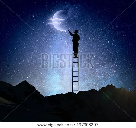 Businesswoman on ladder reaching moon