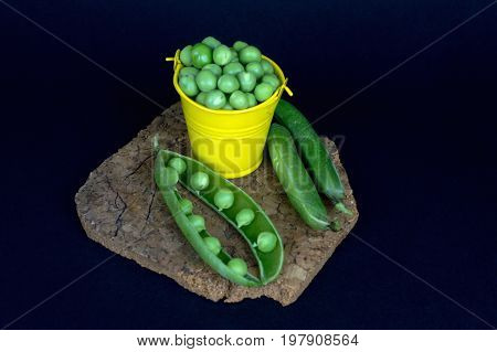 Peas in a bucket on a stand on the black background