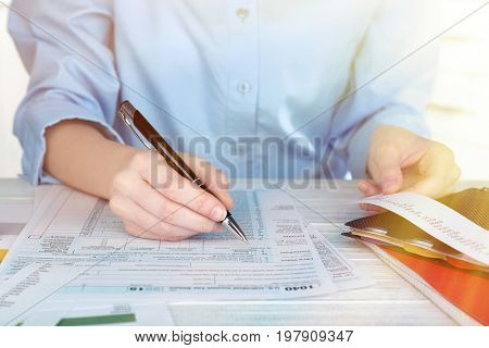 Woman filling in Individual Income Tax Return form at table, closeup