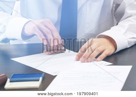 Notary public stamping document in office