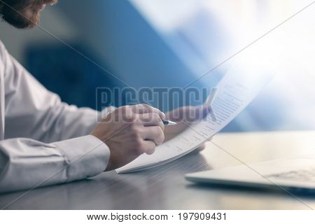 Businessman reading documents at table in office
