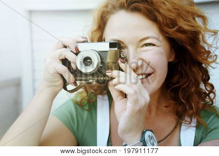 Mature pretty female using film photocamera taking photograph, and smiling