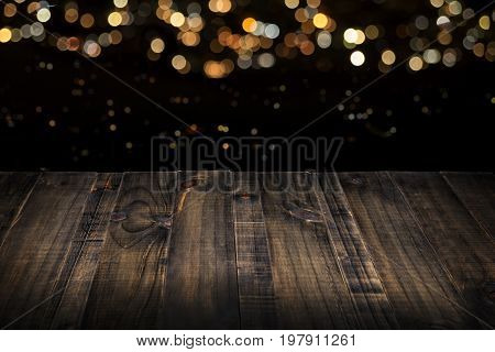 rustic wooden table top with blurred lights in black background