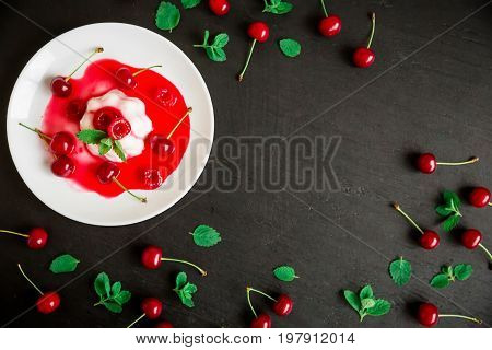 Panna cotta with cherries in white plate on a dark table. Tasty Italian dessert.