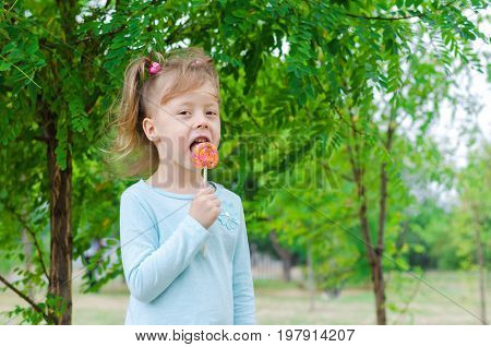 Smiling Little Girl With A Lollipop, Free Space. Beautiful Girl With A Lollipop.