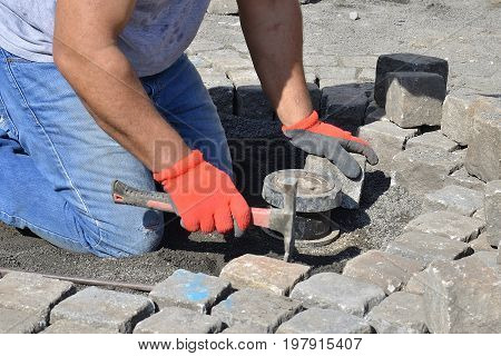 Photo of stonemason who is repairing cobblestone road.