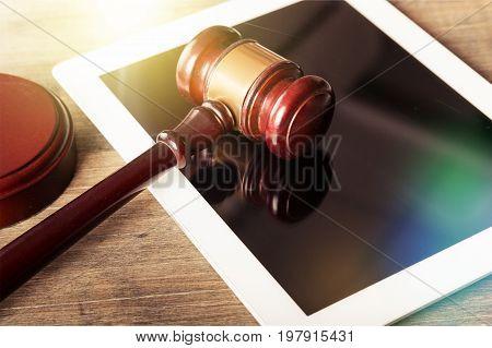 Wooden digital tablet gavel background close-up paper