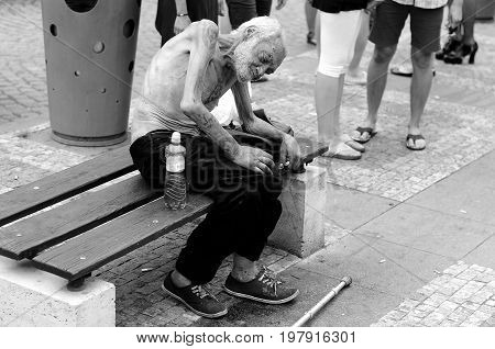 Prague, Czech Republic, August 15, 2015, Editorial photo of skinny homeless beggar who is sitting on bench with indifference other people. Prague, Czech Republic, St. Wenceslaus square