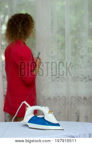 Girl talking on the phone forgetting about the iron on the ironing board