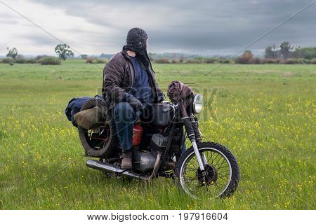 A post apocalyptic man on motorcycle in meadow