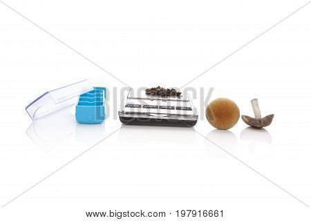 Psychedelic psilocybin medicinical mushrooms pill box digital scale and dry mushrooms isolated on white background. Alternative therapy microdosing.
