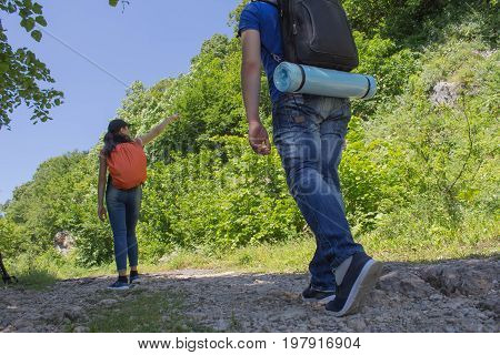 Two young Tourists With Backpacks travel. Active and healthy lifestyle on summer vacation and weekend tour. Group of tourists hitching a ride. Travel adventure and hiking activity