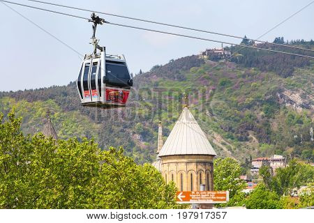 Tbilisi, Georgia - April 29, 2017: Tbilisi red cable car cabin and church tower