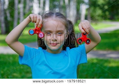 Little beautiful girl is playing with two spinners in hands in outdoors